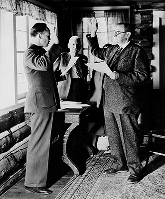 Harlan Fiske Stone (right) being sworn-in as Chief Justice, July 3, 1941. Stone took both oaths in his cottage at the Sprague Hotel before Wayne H. Hackett, the United States Commissioner for Rocky Mountain National Park. Abner Sprague, owner of the hotel, is standing in the background. Stone's first duty as Chief Justice was to lead the nation in a special Fourth of July reading of the Pledge of Allegiance that was broadcast live from outside the park's Stanley Hotel.