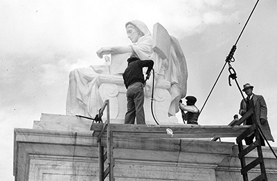 Carvers add finishing touches to Contemplation of Justice, as sculptor James Fraser looks on, November 1935.