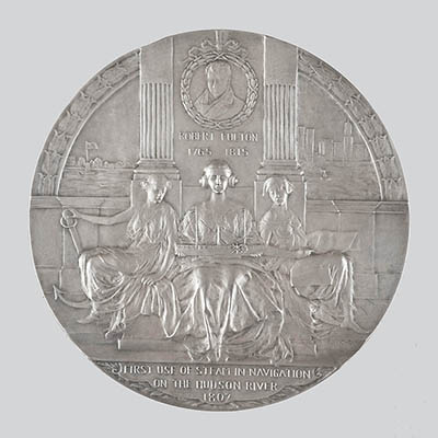 The reverse of the medal depicts three seated allegorical figures, including Commerce (left), Steam Navigation (center), and History (right). Steam Navigation holds a model of Robert Fulton's steamboat, the Clermont. A portrait of Fulton is featured above.